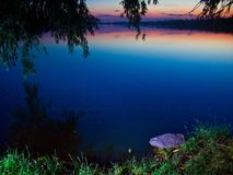 After sunset view of a large, quiet and peaceful summer countryside pond. Romantic lanscape photo of nature Royalty Free Stock Photography