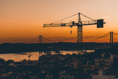 Sunset view of Lisbon with crane and rope bridge Stock Images