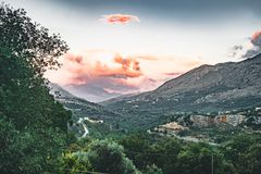 Sunset View on mountains with low hanging clouds orange twilight and green trees. South Crete neat Rethymno, Greece royalty free stock image