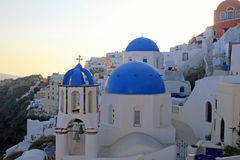 Sunset view with orthodox church,Oia, Santorini island, Greece. Sunset view with white and blue orthodox church in the village of Oia, Santorini island, Greece Royalty Free Stock Image