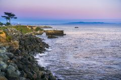 Sunset view of the Pacific Ocean rugged coastline, Santa Cruz, California. Santa Cruz surfing museum in the background; rocky shoreline in the foreground stock photos