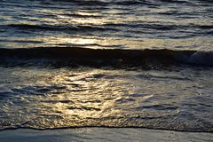 Sunset over the Ocean - View of the red sun sinking into the horizon and waves washing over the sand of the beach. Sunset - View of the red sun sinking into the stock photo