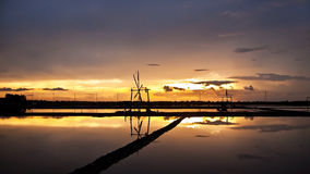 Sunset view of salt farm and wind wheel Royalty Free Stock Photo
