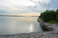 Sunset view of sea with trees and bay walk. And blue sky and sands Royalty Free Stock Image