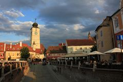 Tower of Council and Small Square in Sibiu under cloudy sky. Sunset view of Sibiu city with Tower of Council in the background and dramatic sky. Small Square stock photo