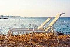 Sunset view from side to two parallel sunchairs and blue sea. Sunset view from side to two parallel sunchairs placed near water. Blue sea with town on background royalty free stock photography