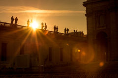 Sunset view of St. Peter`s Basilica in the Vatican. Statues on the Vatican with the sunin the sky during sunset in Rome, Italy stock image