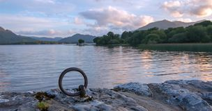 Sunset view of stone boat dock tie up ring of ancient castle ruins McCarthy Mor on Lake Leane on the Ring of Kerry Ireland. Sunset view of stone boat dock tie up stock photos