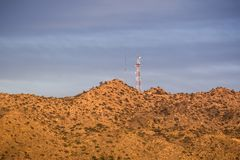 Sunset view of telecommunications tower on top of a hill close to the north border of Joshua Tree National Park, south California stock photography