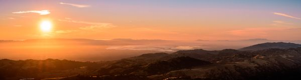 Sunset views of the south San Francisco bay area. And the surrounding hills as seen from the top of Mt Hamilton; a thin layer of fog creates a soft orange royalty free stock photos
