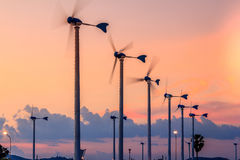 Sunset At Village And Wind Turbines Stock Photo