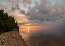 Sunset on the Volga River, the sun sets behind the horizon. The sky is cloudy, rocky coast, covered with trees Stock Photos