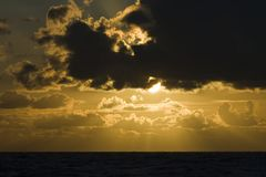 Sunset at Wadden Sea. Golden sunset and dark clouds over Wadden Sea in summer stock photos