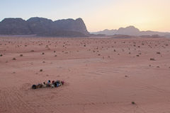Sunset in the Wadi Rum desert, Jordan, with local bedouins and camels on foreground Royalty Free Stock Photos