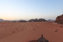 Sunset in the Wadi Rum desert, Jordan, with a man watching the scene from a rock on foreground. Wadi Rum, Jordan - March 24, 2015: Sunset in the Wadi Rum desert stock images