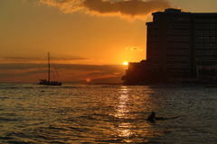 Sunset at waikiki beach. The yacht and surfers are coming back the land royalty free stock photo