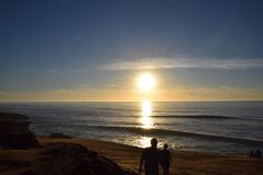 Sunset walk along beach with waves stock photos