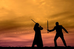 Sunset Warriors. Woman and man sword fighting Stock Image
