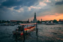 Sunset at Wat Arun. Chao Phraya with Longboat at Sunset. View from a Restaurant with some tourists inside. royalty free stock photos