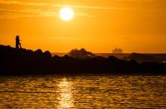 Sunset watchers. Two people watching the setting sun at Ke'e beach on Kauai Island stock photo