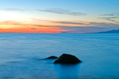 Sunset on water. Sunset on blue water with rock in foreground Royalty Free Stock Photos