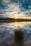 Sunset water reflection on a lake with clouds Stock Photo