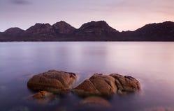 Sunset Water and Rocks. Pink sunset light on a coastal scene - The Hazards, Freycinet (Tasmania, Australia stock photo