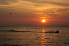 Sunset and water sport. Jet skiing and water parachuting at sunsey Stock Photography