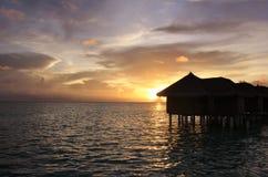 Sunset and water villas, Maldives. Sunset on Maafushivaru island with its water villas. Ari Atoll, Maldives Stock Image