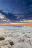 Sunset and the waves lapping on the rocky shore Royalty Free Stock Photography