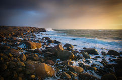 Sunset with waves on rocks Royalty Free Stock Photo