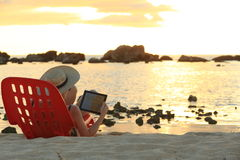 Sunset websurfing. Enjoying the sunshine and the beach with my tablet Royalty Free Stock Image