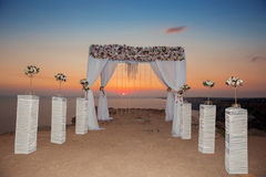 Sunset. Wedding ceremony arch with flowers decorative arrangemen Royalty Free Stock Photo