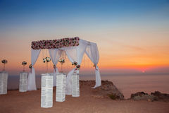 Sunset. Wedding ceremony arch with flowers decorative arrangemen Royalty Free Stock Image