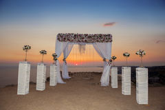 Sunset. Wedding ceremony arch with flowers decorative arrangemen Stock Images