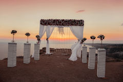 Sunset. Wedding ceremony arch with flowers decorative arrangemen Royalty Free Stock Images