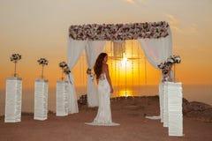 Sunset. Wedding ceremony. Brunette bride under wreath arch with Stock Photos