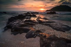 Sunset at Wediombo beach with coral beach stock photography
