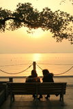 Sunset at West Lake in China. Sunset view with tree branches over two people sitting on a bench at West Lake, China Royalty Free Stock Image