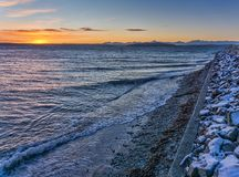 Sunset And West Seattle Shoreline. A view of the setting sun and the West Seattle shoreline in winter stock photos