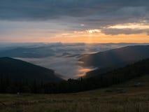 Sunset in west Ukraine. Sundown in Carpathians mountains. Big clouds flowing round dark mountain peaks. The sun behind. Dense clouds. Ukrainian nature landscape stock photography