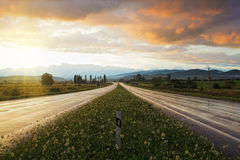 Sunset on wet road. Wet road after rain and sunset over fields Royalty Free Stock Photos