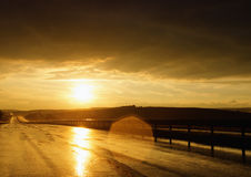 Sunset on wet road. Wet road after rain and sunset over fields Royalty Free Stock Photography