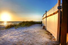Sunset on white sand beach with fence  Royalty Free Stock Photography