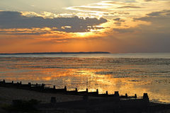 Sunset on whitstable coast. Photo of setting sun over whitstable coast in kent england showing reflecting sun in low tide rock pools Royalty Free Stock Photos
