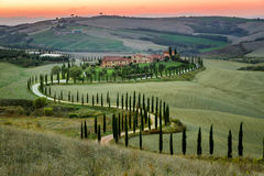 Sunset and winding road with cypresses in Tuscany. Italy stock photo