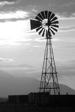 Sunset Windmill. Black and white photo of a windmill as the sun sets over the mountains Royalty Free Stock Photography
