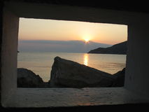 Sunset Through the Window. A sunset in the sea, as seen through a window-like hole in the wall, Sifnos island, Greece stock photography