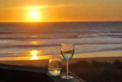 Wine by the Ocean at Sunset. Wine glasses on a wooden railing while the sun is dropping in to ocean Royalty Free Stock Photo