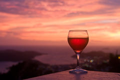 Sunset wine relaxation. Wine glass with caribbean island sunset background Stock Photography